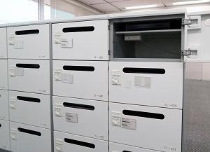 個人ロッカーの高さは約25㎝しかなく、自然と整理整頓が身に付く。この中にノートパソコンやPHSなどを収納して帰宅するため、充電用のAC電源も付いている。扉に開いた穴から、郵便物が入れられる仕組み。