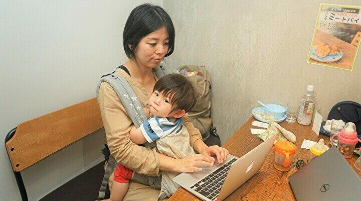 子連れテレワーク実証実験で、1歳の長男を抱っこひもしながらパソコンを扱う女性社員