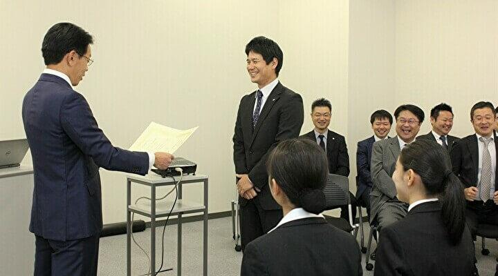 内定者の前で表彰され、中山さん(中央)も後ろの役員も笑顔があふれます